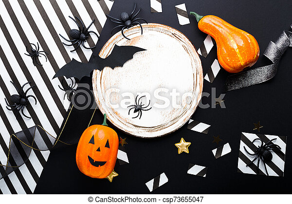 Halloween party invitation mockup, celebration. Frame. Halloween decorations concept with bats, spiders, jack-o'-lantern, stars, confetti, ribbon. Flat lay, top view, copy space on black and white background. - csp73655047
