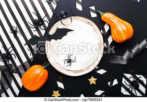 Halloween party invitation mockup, celebration. Halloween decorations concept with bats, spiders, pumpkins, stars, confetti, ribbon. Flat lay, top view, copy space on black and white background. - csp73655341