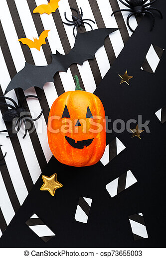 Halloween party invitation mockup, celebration. Halloween decorations concept with bats, spiders, jack-o'-lantern, stars, confetti, ribbon. Flat lay, top view, copy space on black and white background. - csp73655003