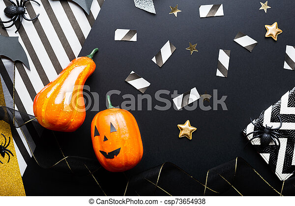 Halloween party invitation mockup, celebration. Halloween decorations concept with bats, spiders, jack-o'-lantern, stars, confetti, ribbon. Flat lay, top view, copy space on black and white background. - csp73654938