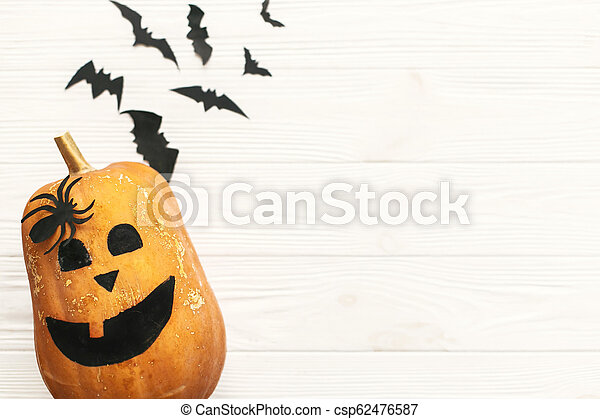 Halloween pumpkin Jack o Lantern flat lay with bats, spiders top view on white rustic wooden background. Trick or treat. Space for text. Season's greeting card mockup. - csp62476587