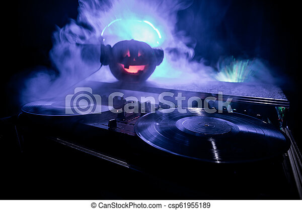 Halloween pumpkin on a dj table with headphones on dark background with copy space. Happy Halloween festival decorations and music concept - csp61955189