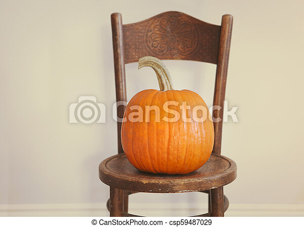 Halloween Pumpkin on a vintage chair - csp59487029