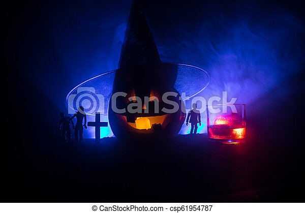 Halloween pumpkin with carved face and glass of whiskey with ice on a dark toned foggy background with zombies. Decorated. Selective focus - csp61954787