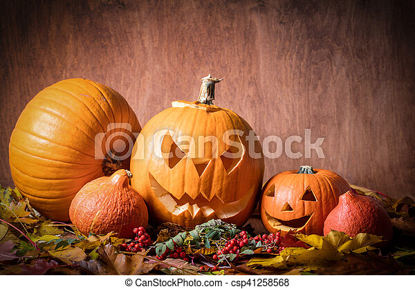 Halloween pumpkins, carved jack-o-lantern in fall leaves - csp41258568