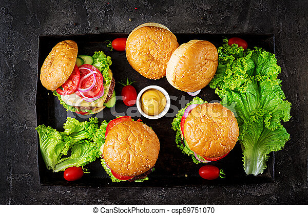 Hamburger with beef meat burger and fresh vegetables on dark background. Tasty food. Top view - csp59751070