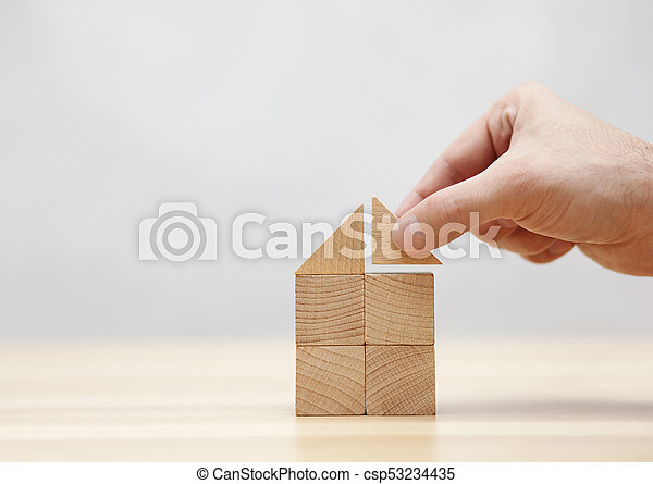 Hand building house with wooden blocks - csp53234435