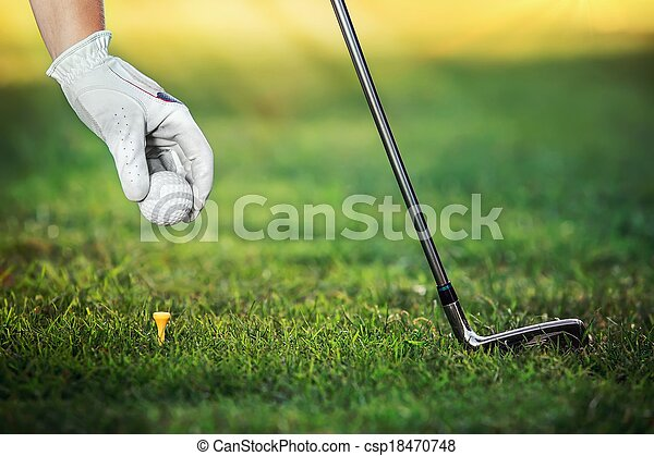 Hand hold golf ball with tee on course, close-up   - csp18470748