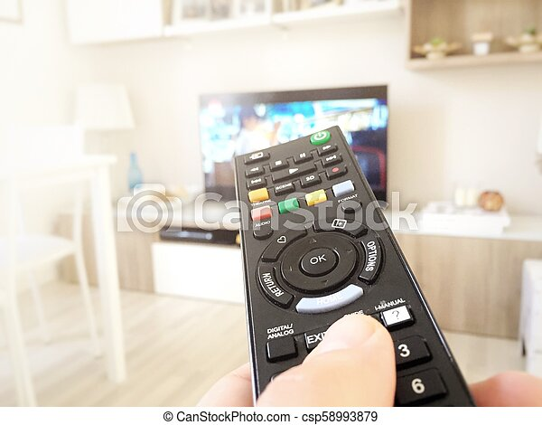 Hand hold the television remote control - csp58993879