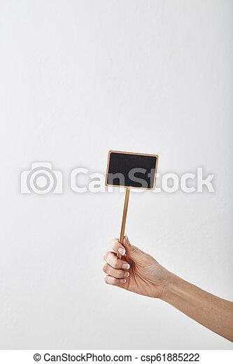 hand holding a blank blackboard label - csp61885222