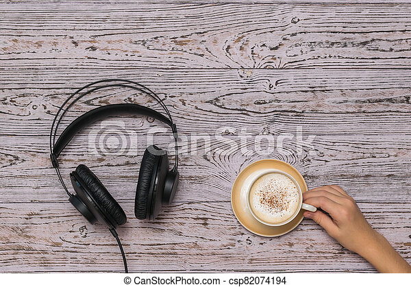 Hand holding a coffee Cup and black wired headphones on the wooden table. - csp82074194