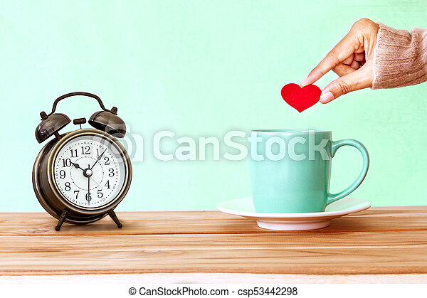 hand holding a Coffee cup mug on wooden table , Romance and love background . Happy and relax concept - csp53442298