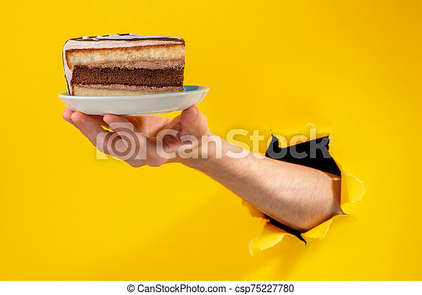 Hand holding a piece of cake on a plate through a torn hole in yello background - csp75227780