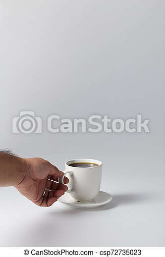 Hand holding a white cup of coffee - csp72735023