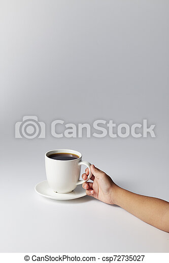 Hand holding a white cup of coffee - csp72735027
