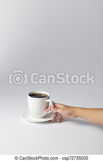 Hand holding a white cup of coffee - csp72735030