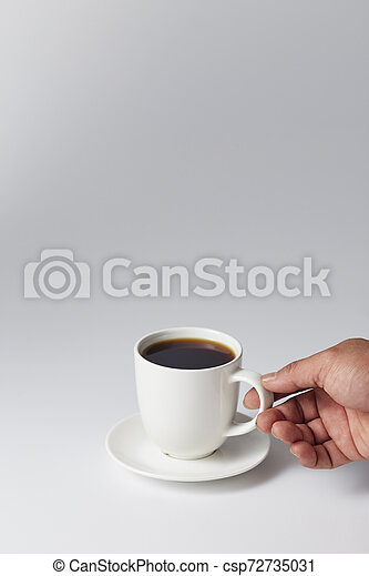 Hand holding a white cup of coffee - csp72735031