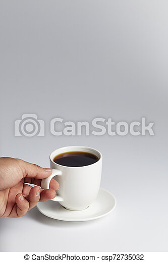 Hand holding a white cup of coffee - csp72735032