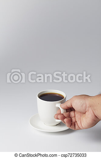 Hand holding a white cup of coffee - csp72735033