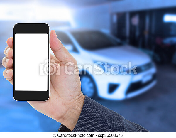 Hand holding blank screen mobile phone with blur car background - csp36503675