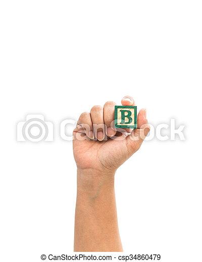 "Hand holding colorful alphabet blocks ""B"" isolated on white - csp34860479"