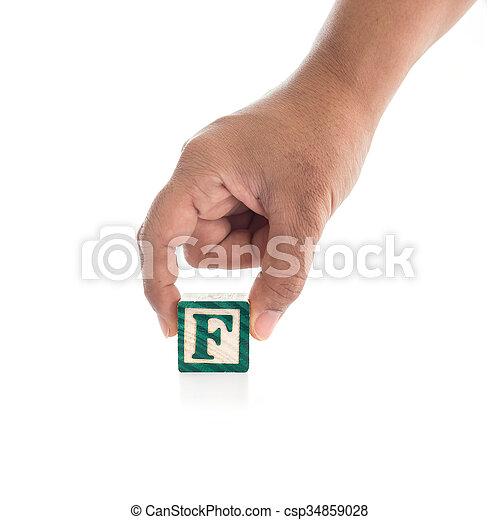 "Hand holding colorful alphabet blocks ""F"" isolated on white background - csp34859028"