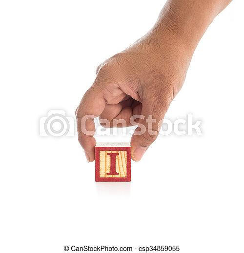 """Hand holding colorful alphabet blocks """"I"""" isolated on white - csp34859055"""
