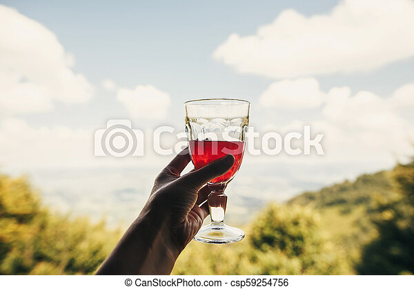 hand holding cranberry juice in glass cup on background view of mountains and sky. stylish red drink on porch. summer vacation and relax concept. travel and wanderlust. space for text - csp59254756