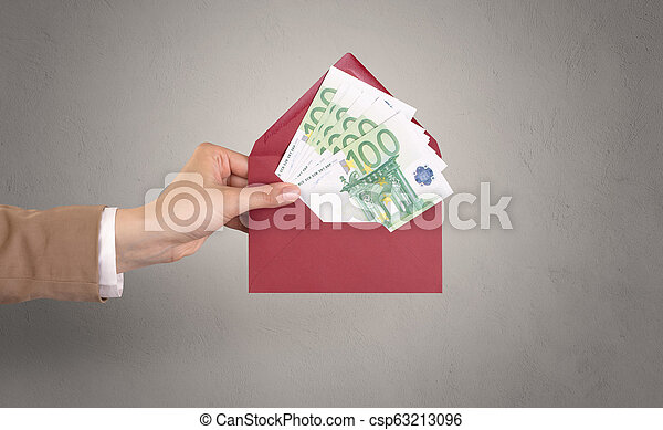 Hand holding envelope with empty wall background - csp63213096