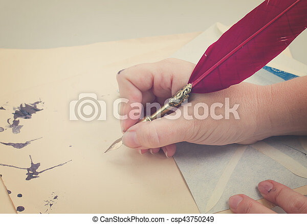hand holding feather pen - csp43750249