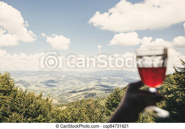 Hand holding glass with lemonade drink, focus on beautiful landscape of woods and mountains. Space for text. Travel and vacations - csp84731621