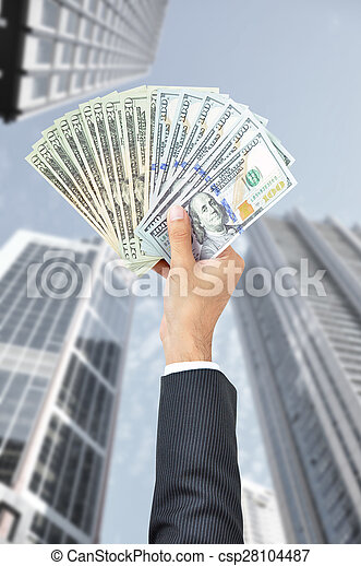 Hand holding money - United States Dollars (or USD) - on building background - csp28104487