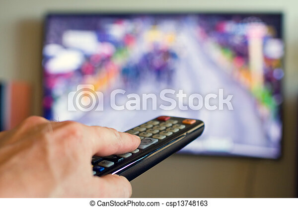 Hand holding TV remote control with a television in the background. - csp13748163