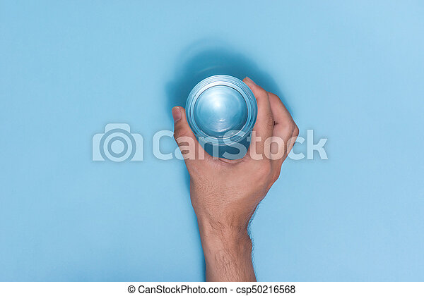 Hand holding water glass on blue background. - csp50216568