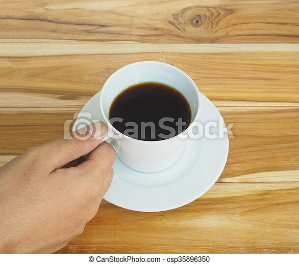 hand holding white cup of coffee - csp35896350