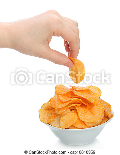 Hand holds a potato chip with the bowl of potato chips on white background - csp10810359