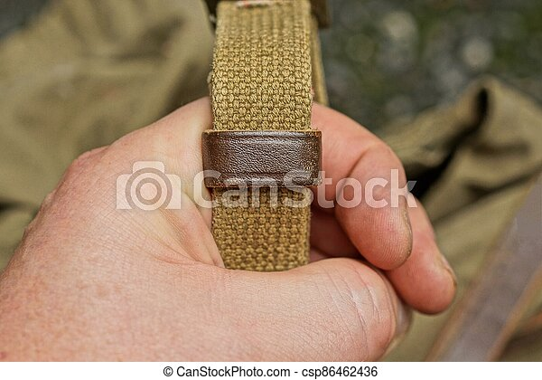 hand holds an old long green fabric harness - csp86462436