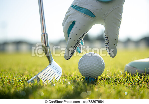 Hand in glove placing golf ball on tee - csp78397984