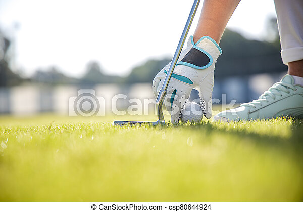 Hand in glove placing golf ball on tee - csp80644924