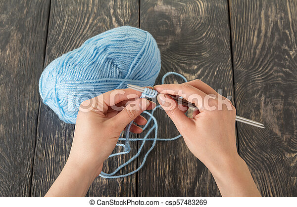 Hand Knitting Yarn And Knitting Needles A Set Of Initial Series Loops On Wooden Surface