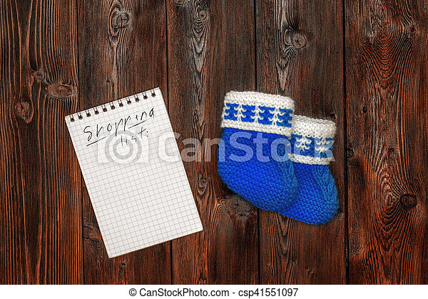 Hand made baby booties, blank notebook with shopping list, copyspace - csp41551097