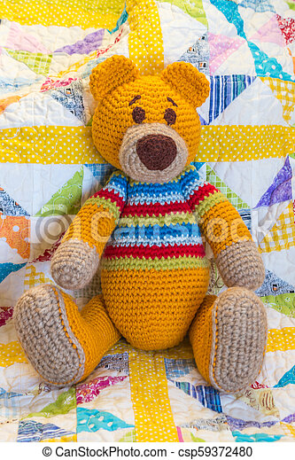 hand made crochet teddy bear sitting on quilt cover - csp59372480