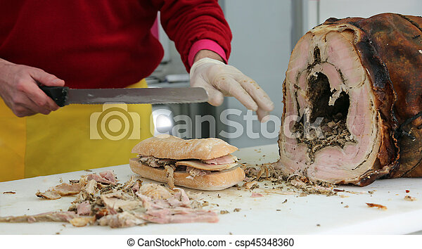hand of chef slicing the meat of pork to prepare a sandwich - csp45348360