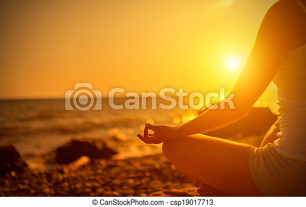 hand of  woman meditating in a yoga pose on beach at sunset - csp19017713