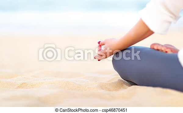 hand of woman practices yoga and meditates on beach - csp46870451