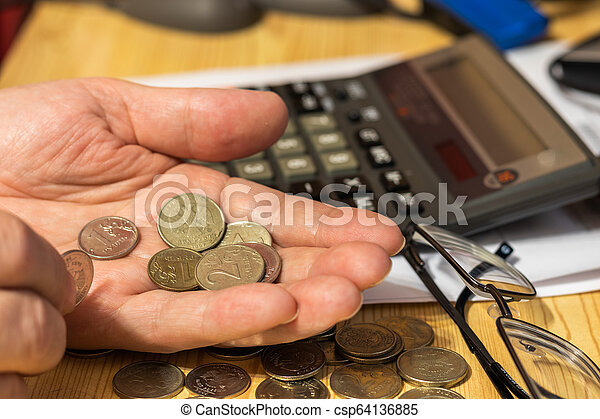 Hand pensioner, glasses, calculator and coins on the table surface. translation of the inscription: the identity of the pensioner - csp64136885