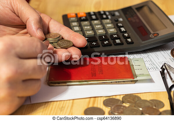 Hand pensioner, glasses, calculator and coins on the table surface. translation of the inscription: the identity of the pensioner - csp64136890