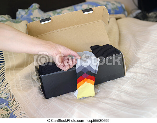 Hand Picking Up Socks - csp55530699