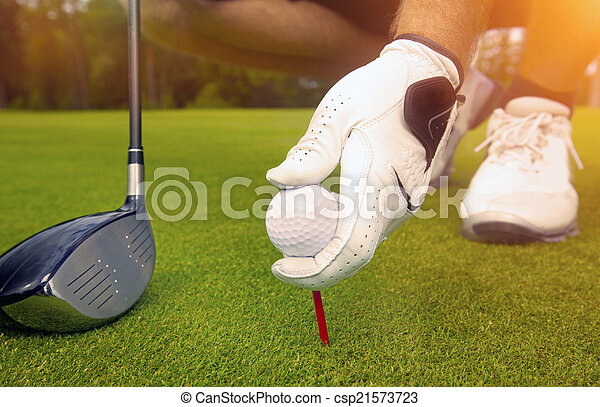 hand placing a tee with golf ball - csp21573723