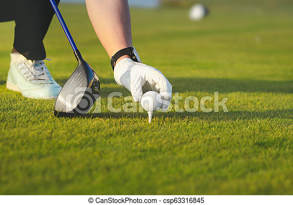 hand placing golf ball on tee - csp63316845